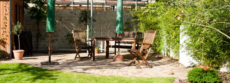 Sitzplatz aus Natursteinpflaster vor einer alten Wand