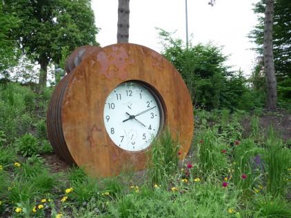 Sinnesgarten riesige Uhr als Gartenskulptur